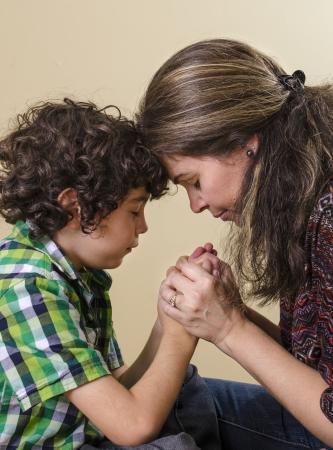ni�o orando: La reverencia, la devoci�n y el amor de una familia hispana hacia su Salvador en el cielo Foto de archivo