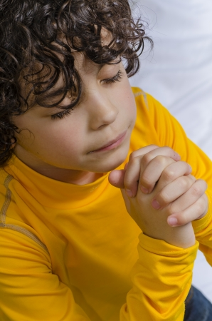Latin young boy praying and praising God photo