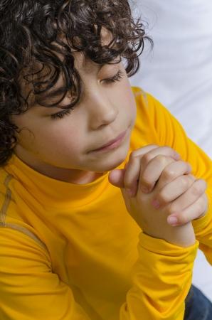 Latin young boy praying and praising God