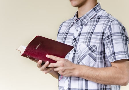 Young man standing and reading the bible photo