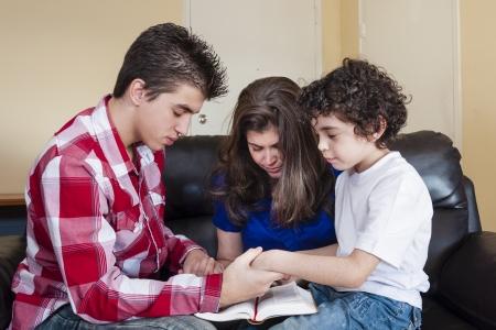 prayer hands: Famiglia cristiana pregare nella loro devozione quotidiana a casa