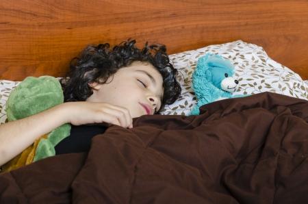 Boy sleeps quietly with his stuffed animals