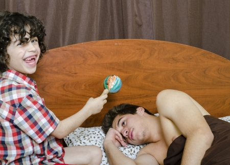 Young boy awakes his elder brother by making noises Stock Photo - 16409364
