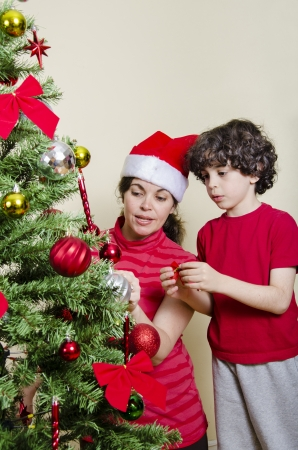 Single mother and son putting together a Christmas Tree photo