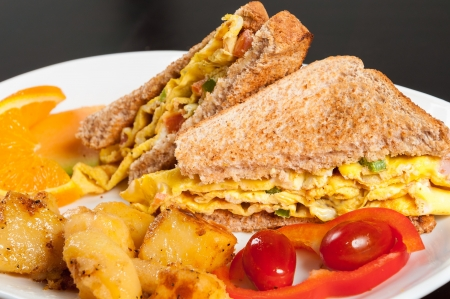 Omelette sandwich with green peppers and side of potatoes photo