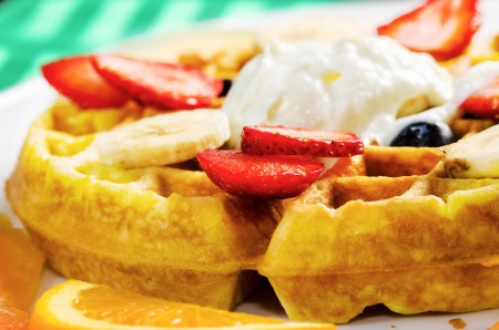 Delicious combination of waffle, ice cream and varied fruits photo