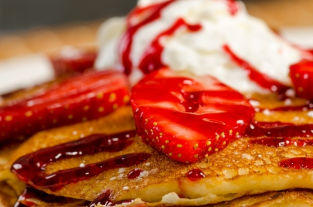 Colorful view of a tasty pancake with ice cream, strawberries and syrup photo