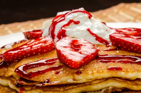 Colorful view of a tasty pancake with ice cream, strawberries and syrup Stock Photo - 18453190
