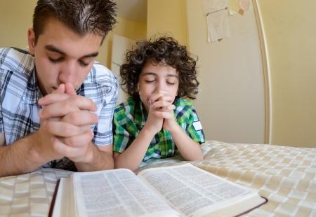 orando: Los muchachos orando y alabando a Dios, la familia santa ejercer su fe en casa.
