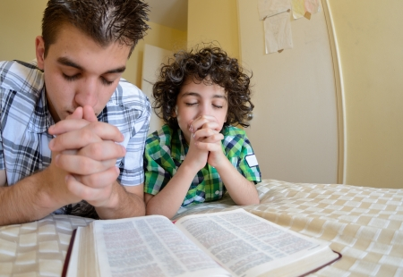 jesus praying: Young boys praying and praising God, Godly family exercising their faith at home.