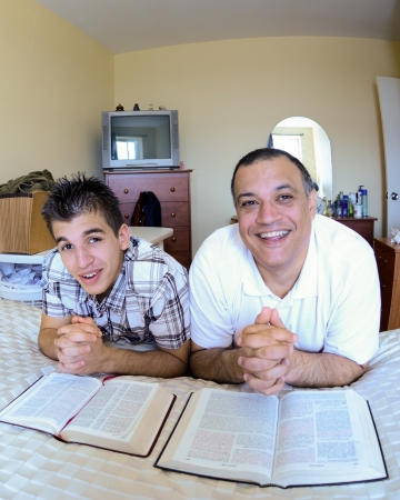 Father and son are surprised while praying and praising God, Christian joy in a united godly family photo
