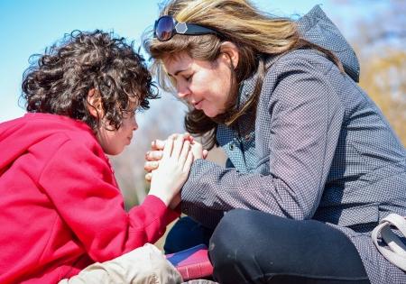 familia cristiana: Familia Am�rica reverenciar y alabar a Dios al aire libre. Fiel oraci�n de una familia latina, incluyendo a un ni�o Foto de archivo