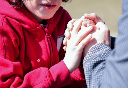 Mother and son hands joined in prayer. Latin family reverencing and praising God. Guidance in a religious lifestyle. Stock Photo