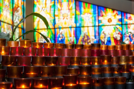 Beautiful scene of candles for prayers in a Catholic Church  Nice background of a stained glass window