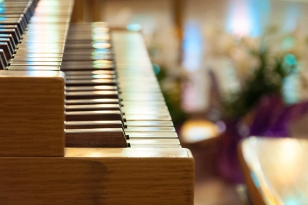 Piano or organ in a catholic church used for praising and reverencing God  Beautiful background of stained glass