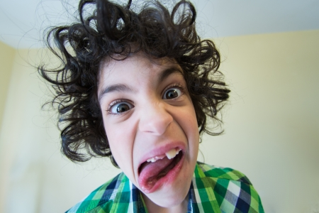 Hispanic child making faces and mocking his siblings