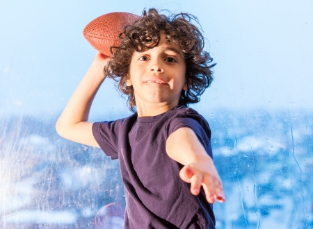 go inside: Hispanic boy plays football inside to entertain himself. A bad weather impedes him to go outdoors