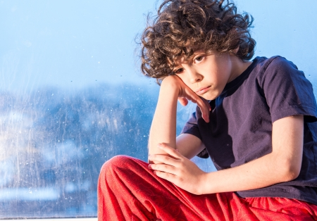Hispanic Junge sehr traurig, weil er will ouside spielen und es regnet. Rainy day Folge. Kleines Kind drinnen wegen des Wetters Standard-Bild - 19250409