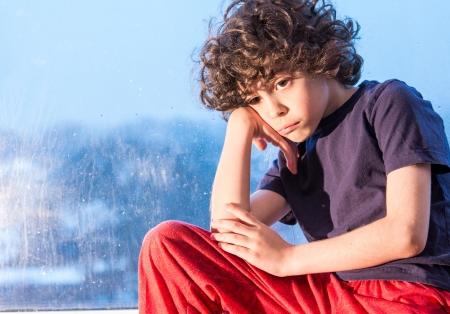 Spaanse jongen heel verdrietig want hij wil lawaai buiten te spelen en het regent. Regenachtige dag consequentie. Weinig kind binnenshuis vanwege het weer Stockfoto - 19250409