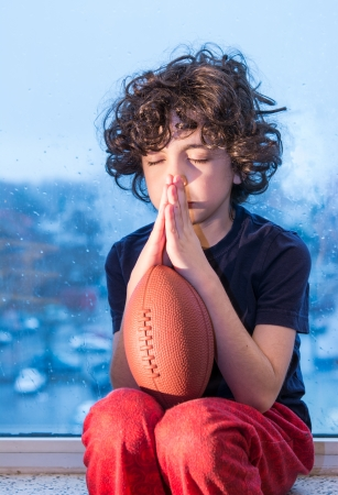 ラテン系少年が彼の家の外で遊ぶことができるへの祈り。雨の日の結果として彼の家の中