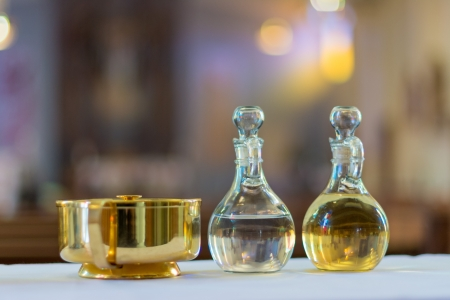Symbols of the traditions of a Catholic Church  Holy water and oil for unction photo