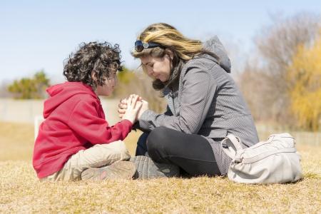family praying: Madre soltera que enseña a su hijo y glorificar a Dios por medio de la oración Foto de archivo
