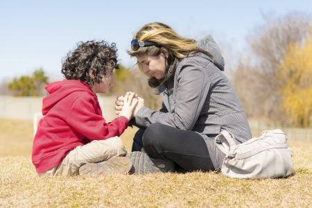 christian prayer: Single mother teaching her son and glorifying God through prayer