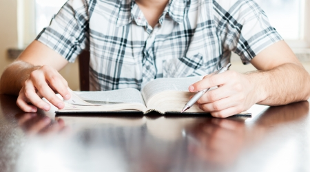 study: Christian teenager in his daily devotional. Young man reading the Holy Bible