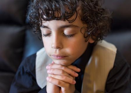 Hispanic child praying and praising God photo