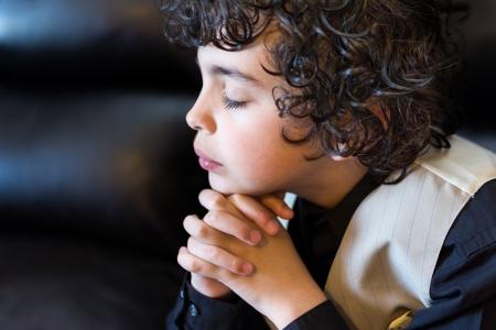 Hispanic child praying and praising God Foto de archivo