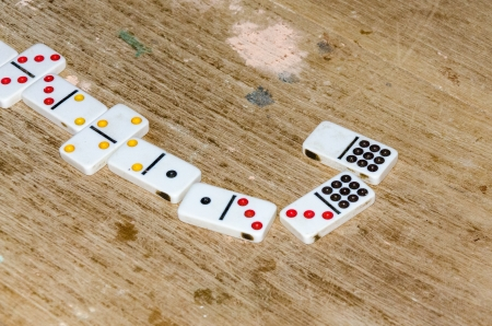 passtime: Row of matched dominoes in a rustic table Stock Photo
