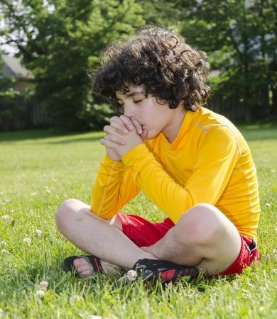 child praying: Hispanic Child Praying Outdoors Stock Photo