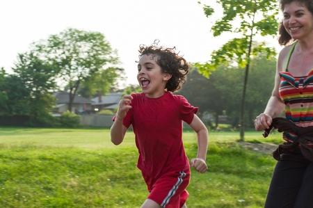 madre soltera: Madre soltera de correr y se divierte con su hijo en un parque Foto de archivo
