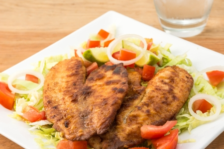 broiling: Breaded Tilapia fillet over a plate of garden salad