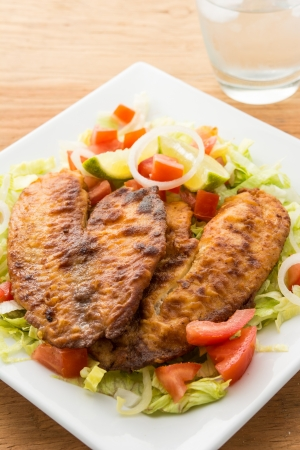 Breaded Tilapia fillet over a plate of garden salad photo