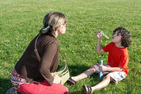 madre soltera: Madre soltera y su hijo se divierten en un parque durante el verano del muchacho que sopla burbujas de jab�n de la familia feliz al aire libre