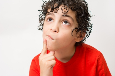 disheartened: Sad Hispanic boy looking away  White background and a lonely boy who looks dishearted and bored  Worried little child with curly hair and wearing a red T-Shirt  Stock Photo
