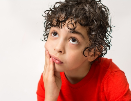 glum: Sad Hispanic boy wondering what could have happened  White background and a lonely boy who looks intrigued and pensive  Little child with curly hair and wearing a red T-Shirt