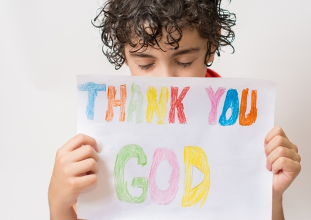 christian worship: Young Hispanic child praying He is thanking God and Jesus for the peace he experiments in his life  Solid relationship with the Savior since childhood