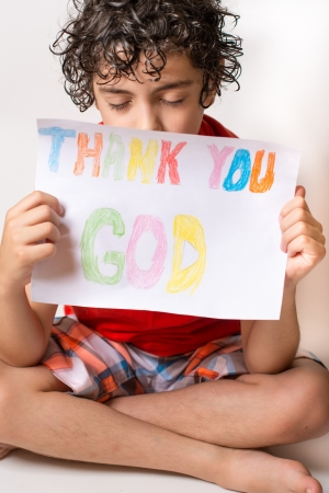 inadequate: Young Hispanic child praying He is thanking God and Jesus for the peace he experiments in his life  Solid relationship with the Savior since childhood