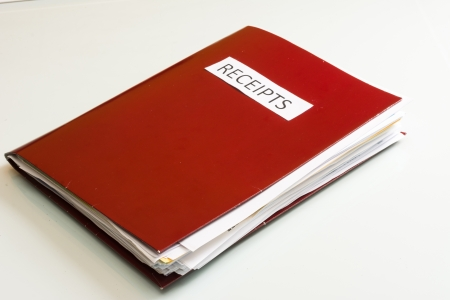 Folder full of business papers  bills, accounts receivable,invoices,receipts,etc  Blue folder with a business paperwork and red tape  Stock Photo - 22118119