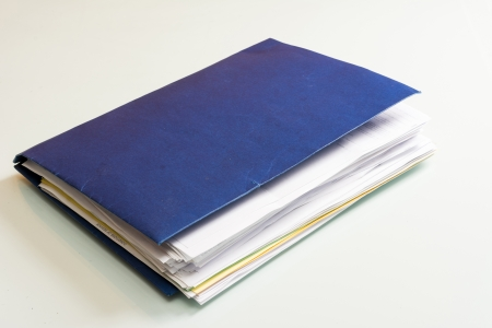 Folder full of business papers  bills, accounts receivable,invoices,receipts,etc  Blue folder with a business paperwork and red tape  Stock Photo - 22118167