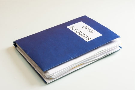 Folder full of business papers  bills, accounts receivable,invoices,receipts,etc  Blue folder with a business paperwork and red tape Stock Photo - 22118207