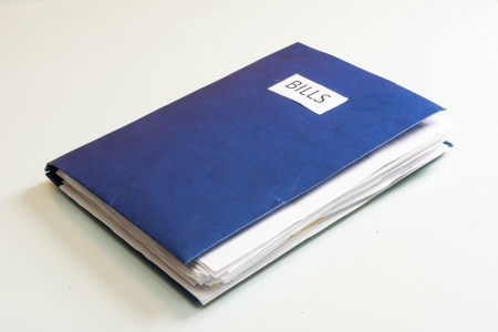 Folder full of business papers  bills, accounts receivable,invoices,receipts,etc  Blue folder with a business paperwork and red tape  photo