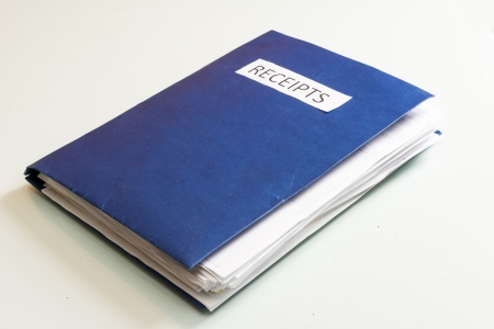 Folder full of business papers  bills, accounts receivable,invoices,receipts,etc  Blue folder with a business paperwork and red tape Stock Photo - 22118218