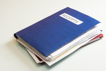 Folder full of business papers  bills, accounts receivable,invoices,receipts,etc  Blue folder with a business paperwork and red tape  Stock Photo - 22118228