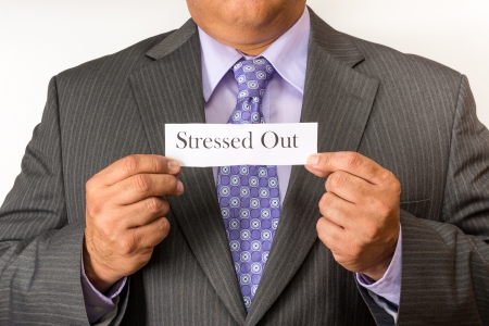 Business man holding a sign of stressed out  Worsening scenario for white collar workers as technology and flatter structures are implemented in the new business concepts