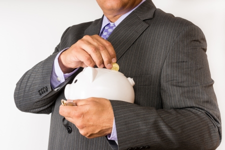 Hispanic man torso  Holding a piggybank and saving some dollars  Man wearing suit and saving money  The habit of saving in a white collar man photo