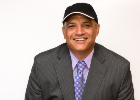 Smiling Hispanic man dressed in a business suit and wearing a cap  Space for some text in the hat  Happy business man with a positive gesture on his face  Stock Photo