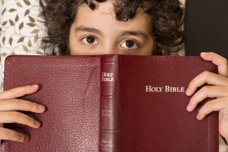 creador: Ni�o hispano joven leyendo y estudiando la Biblia en casa Devocional diario y la reverencia de un ni�o toma un descanso y meditaci�n de la Palabra de Dios, del amor de un ni�o por su creador en el cielo